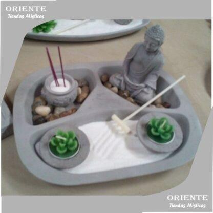 jardin zen con dos velas cactus un rastrillo color natural arena blanca un buda de cemento y cuenco que se utiliza para portasahumerios chinos tambien tiene piedras en su interior