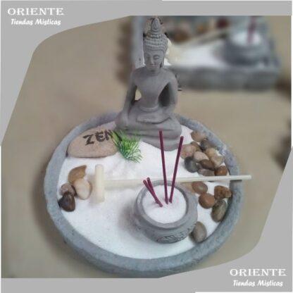 jardin zen redondo con buda con un cuenco portasahumerio y piedras naturales color marron tiene en su interior arena blanca fina