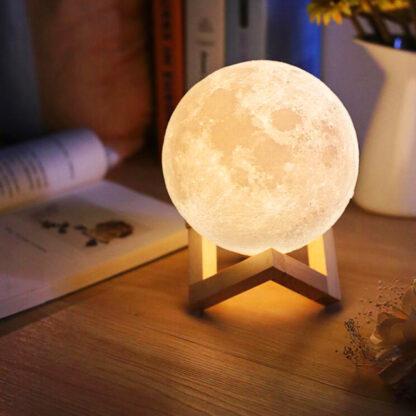 lampara de luna recargable 3d sobre mesa de madera y libro abierto al costado la luna esta encendida